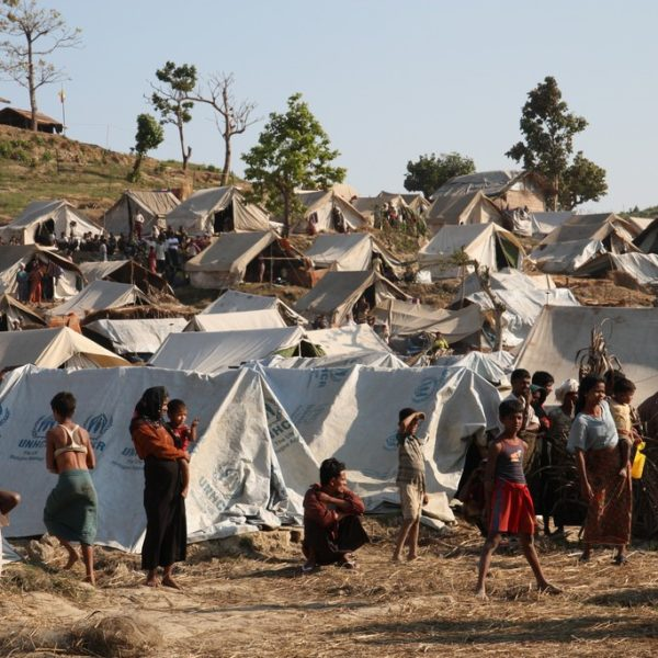 A Rohingya camp in Rakhine state. People mill around white tents on dry ground.