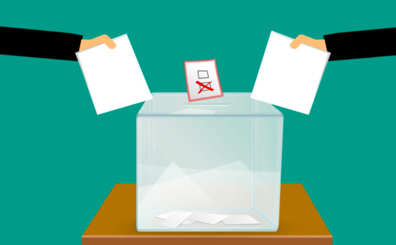 Two cartoony hands drop paper in a ballot box. The background is teal.