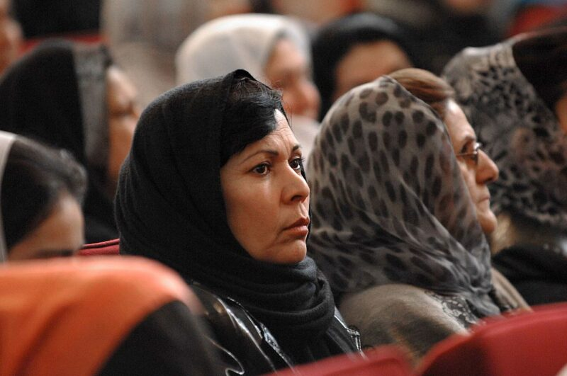 Afghan women in various colourful scarves stare into the distance.