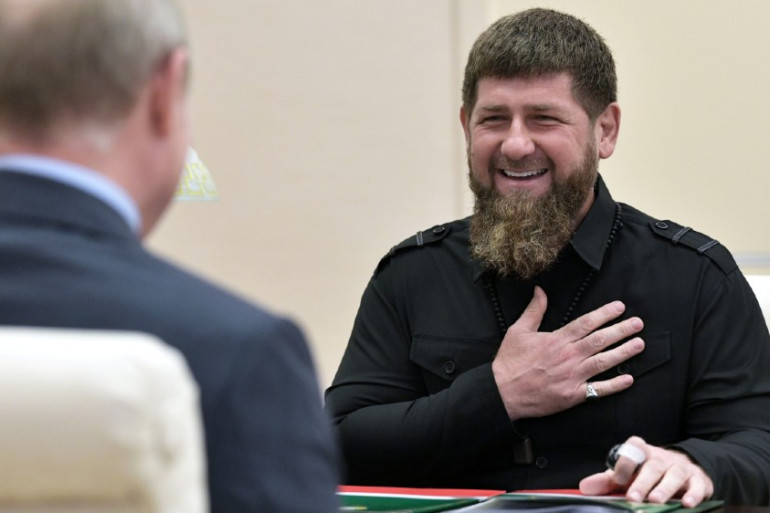 Chechnyan president Ramzan Kadyrov laughs and sets a hand over his heart. He sits across from Vladimir Putin, seen from the back.