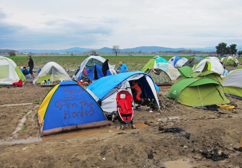 """A collection of tents in a muddy field. One has been written on: """"Help us. Open the borders."""""""