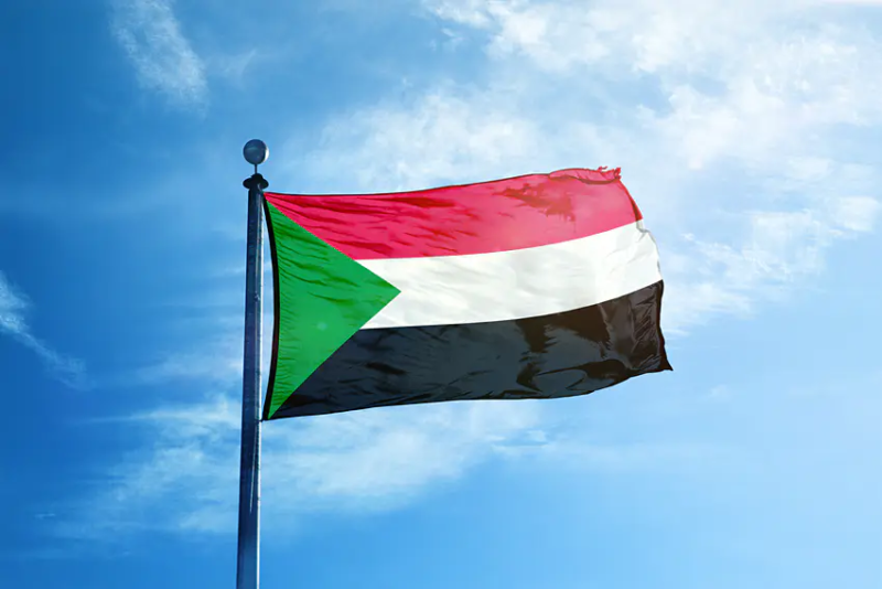 A slightly worn Sudanese flag against a blue sky.