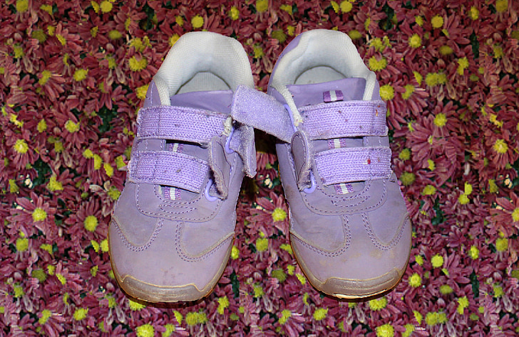 A pair of purple, velcro kids' shoes.
