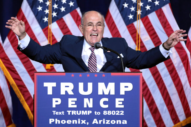 """Rudy Giuliani, gesturing grandly in front of two giant American flags, as if to hold off applause. He is smiling and stands behind a """"Trump Pence"""" campaign sign."""