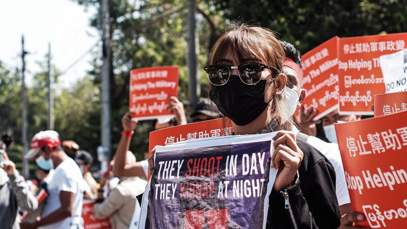 """A crowd of protestors against the coup in Myanmar. Red signs read """"Stop helping the military"""" in four languages. A woman at the front holds a sign: """"They shoot in day, they kidnap at night."""""""