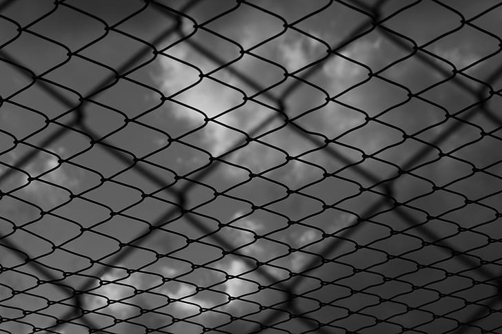 Black prison fence wires double-layered against a dark, cloudy sky.