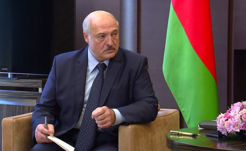 President Lukashenko. He sits, as if mid-debate or interview, next to a Belarusian flag.