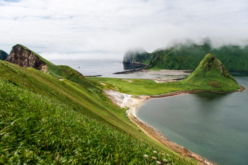 A photograph of the Kuril Islands: green grass forms rolling hills over blue waters.