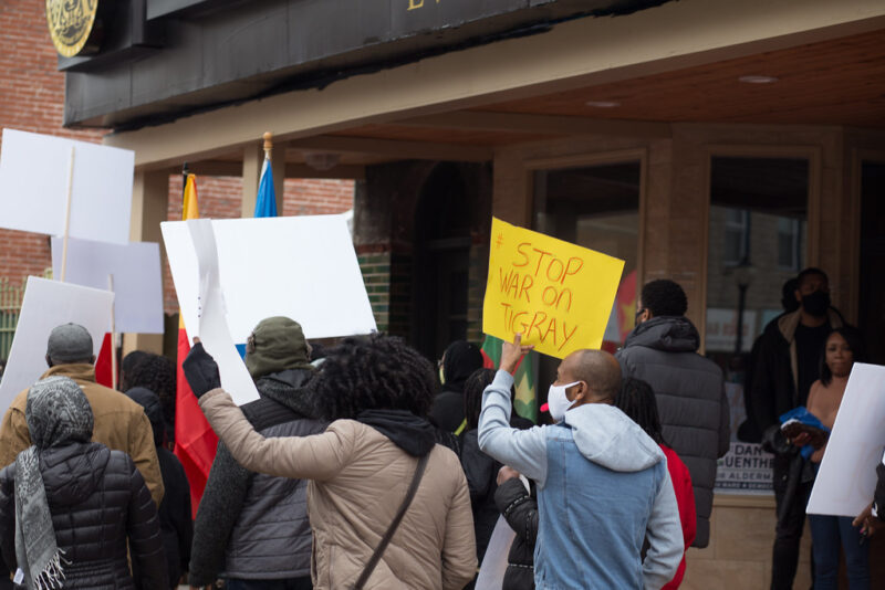 """Missourians gather to protest the war in Tigray. Seen from the back, their signs are illegible, except for one reading """"Stop war on Tigray."""""""