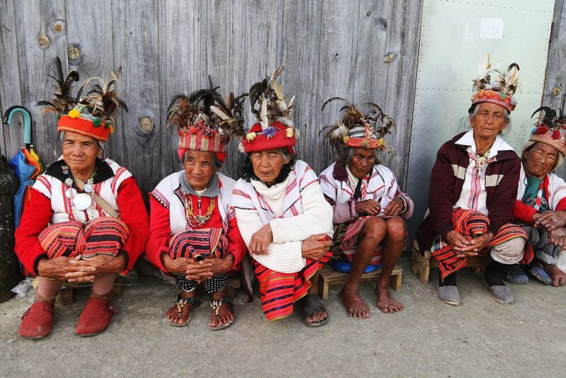 Igorot women sit on concrete against a wooden wall. They wear bright red and white clothing and hats decorated with feathers..