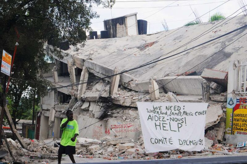 A Haitian man walks past a sign requesting help and supplies in the aftermath of the 2010 quake.