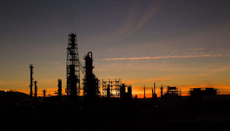 An oil refinery at sunset. The dim orange glow at the horizon makes it seem like the refinery is burning.