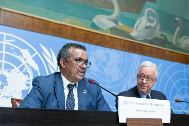Tedros gives a speech against a U.N. logo background. His placard identifies him as the W.H.O. Director General.