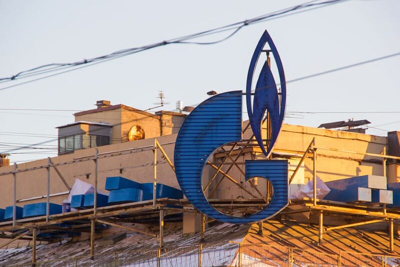 The Gasprom logo, a blue G drawn to look like a lit lighter, on a rig.