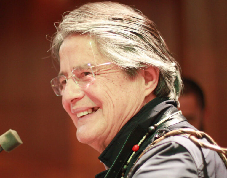 President Guillermo Lasso, a smiling man with silvering hair and clear-framed glasses. He wears a necklace of beads.