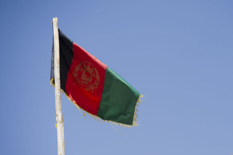A fringed Afghan flag stands against a clear sky.