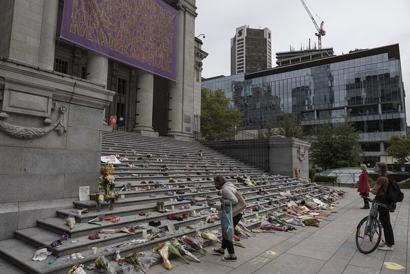A memorial for the Kamloops victims in Vancouver. Bouquets cover every step of a long, decorative exterior flight.